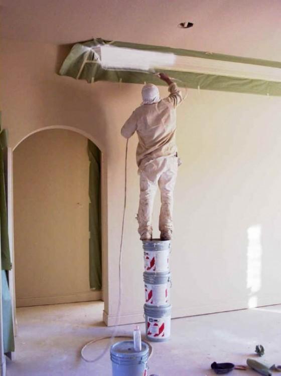 hombre se sube a botes de pintura para alcanzar el techo y pintarlo