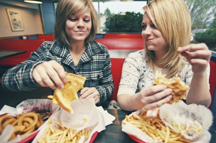 mujeres comiendo comida rapida y grasosa