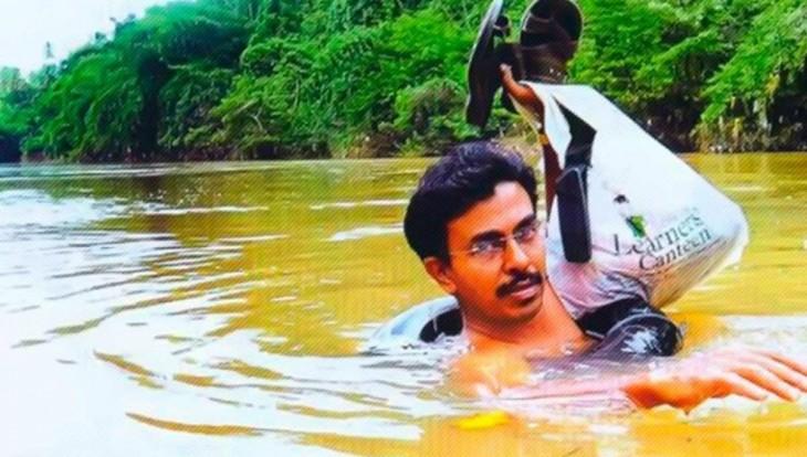 maestro atravesando el rio con sus pertenencias en las manos