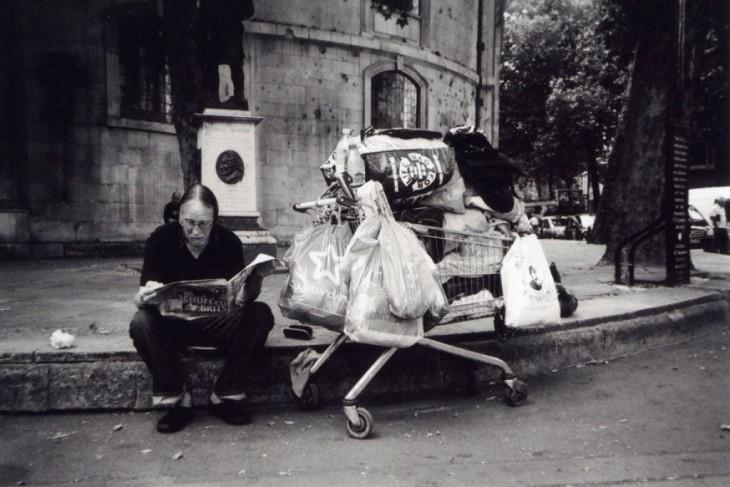 Fotografía de un vagabundo sentado en el suelo con un carro lleno de bolsas en un lado