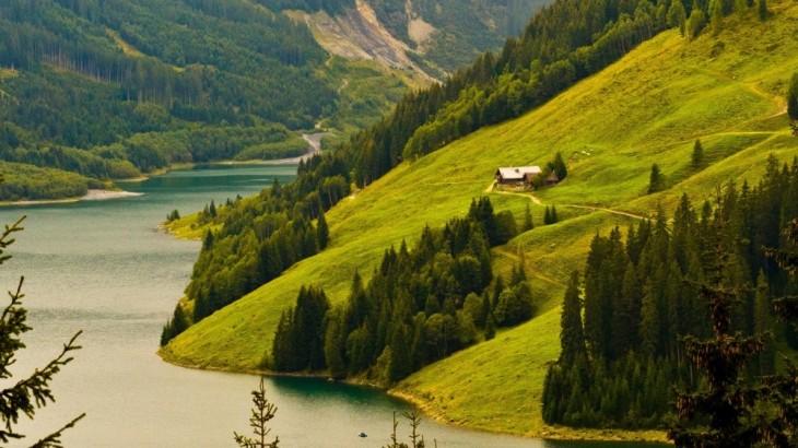 Casa en medio de pastos verdes cerca de un lago