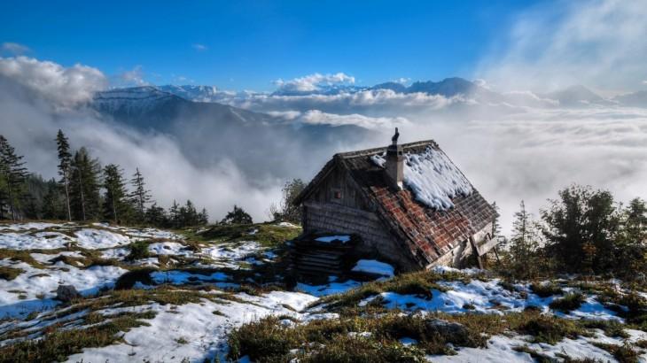 Pequeña casa con un poco de nieve encima de ella rodeada de niebla cerca de unas montañas