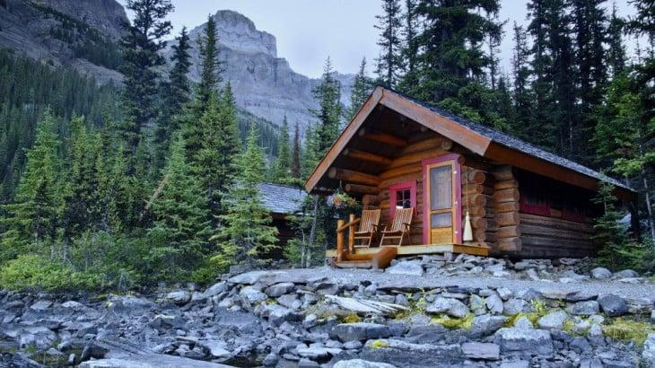Casa de madera con pinos y montañas en su alrededor