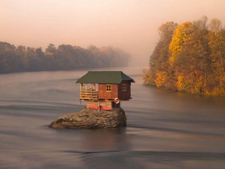 Fotografía de una casa construida en medio de un mar sobre una gran piedra