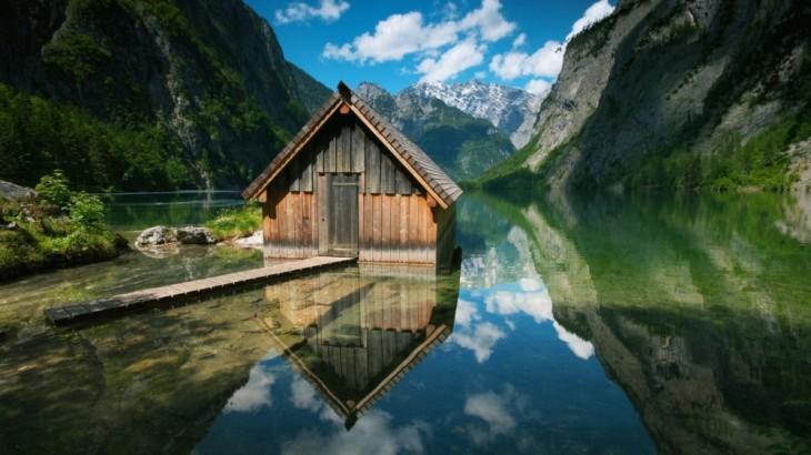 Casa en medio de un lago en medio de dos montañas