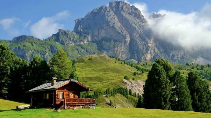 casa de madera con montañas y áreas verdes a su alrededor