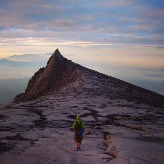 Johnny caminando por un paisaje desértico hasta un acantilado
