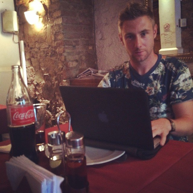 Johnny Ward sentado detrás de su laptop en un restaurante