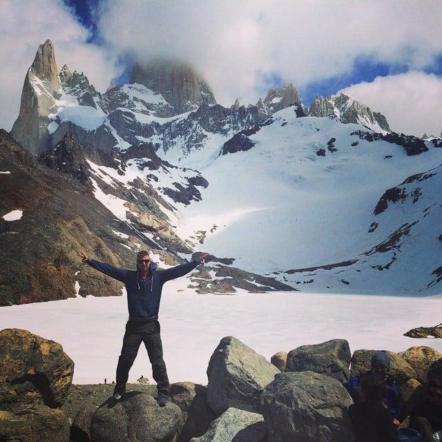 Un chico con las manos extendidas a los lados en unas montañas nevadas