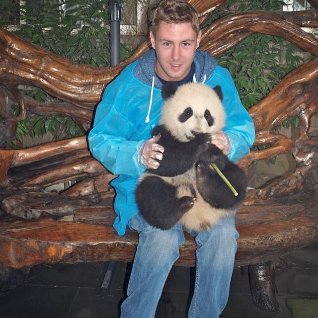 Johnny Ward con un panda en su piernas durante su viaje en China