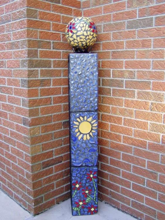 Florero y esquinero hecho con bloques de cemento con diseños de flores y un sol