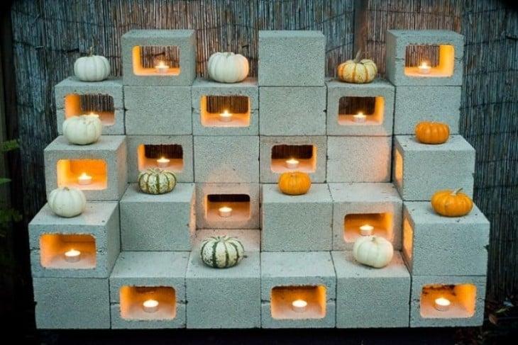 Altar hecho con bloques de cemento con veladoras y calabazas