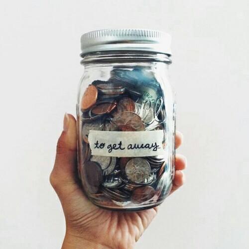 Mano con un vaso lleno de dinero ahorrando