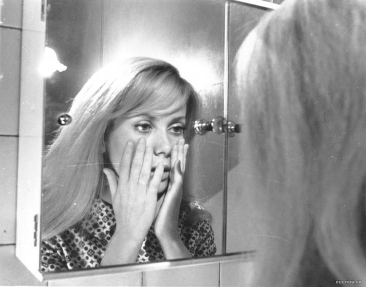 Mujer sosteniendo su cara mientras se ve en el espejo