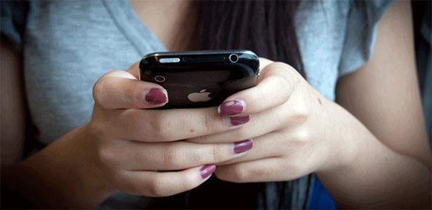 Manos de una mujer mandando mensajes desde su celular