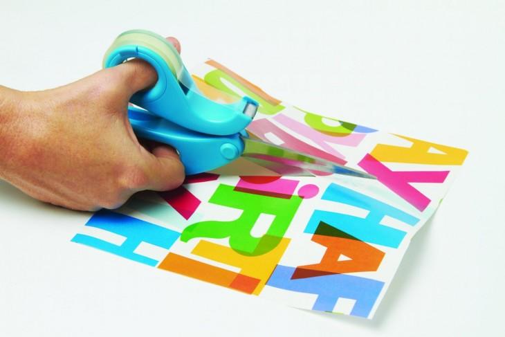 Combo de tijeras con cinta adhesiva cortando un papel
