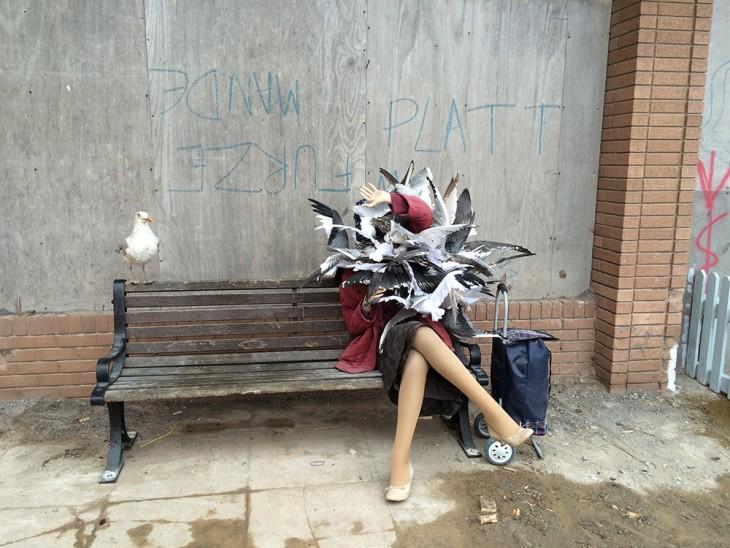 banca con la obra de una mujer con pájaros sobre ella en Dismaland
