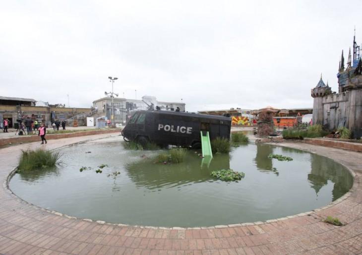 Lago con una camioneta de policía en el centro frente al castillo en el parque Dismaland