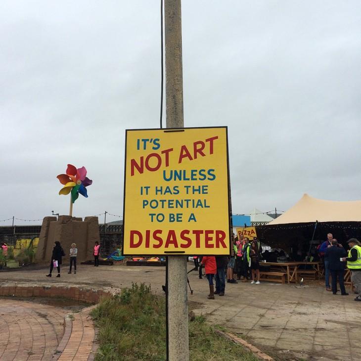 Letrero de aviso afuera del parque de diversiones Dismaland