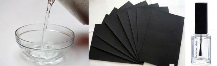 Imagen con un recipiente de agua, papel negro y esmalte transparente