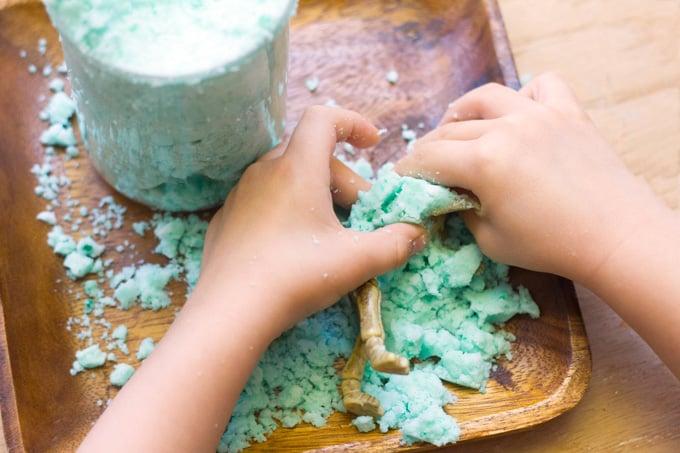 Manos de un niño con una masa cubriendo un juguete