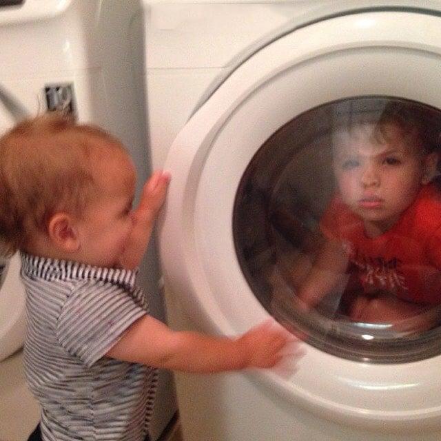 Un niño dentro de una lavadora en donde otro lo mira desde afuera