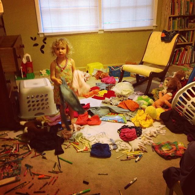 Niña en un cuarto rodeada de muchas cosas tiradas en el suelo