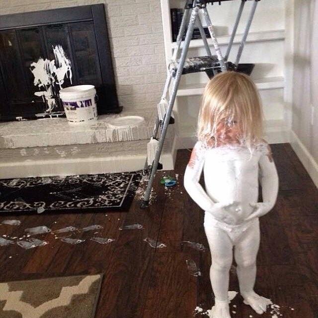 Niña con el cuerpo pintado de blanco con pequeñas manchas en las paredes y el piso