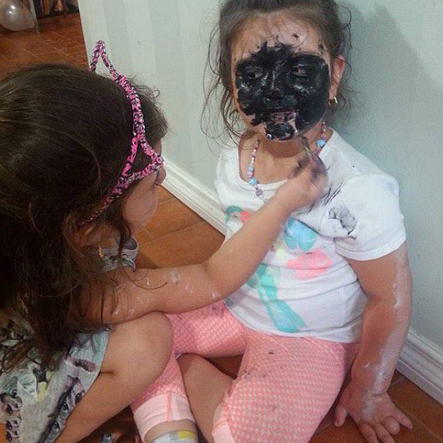 Niña pintando la cara de negro de otra niña