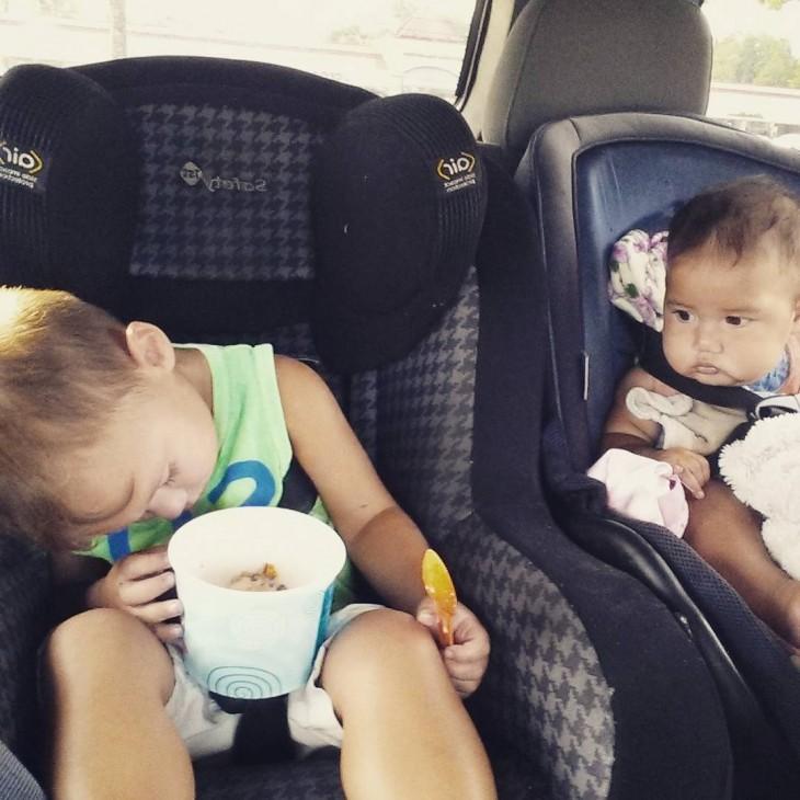 dos niños sentados en la parte trasera de un coche en donde un niño esta dormido