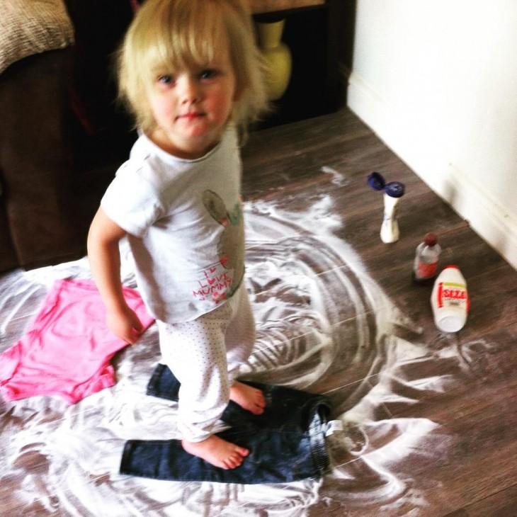 Niño arriba de un pantalón sobre un piso lleno de crema y polvo blanco