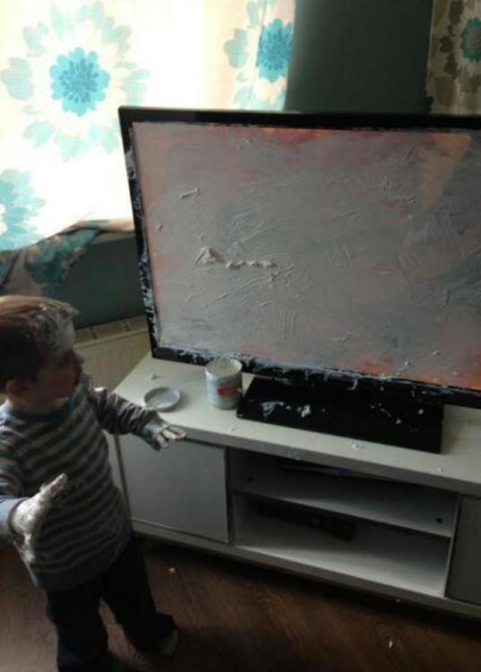 Niño frente a un mueble con una televisión llena de crema