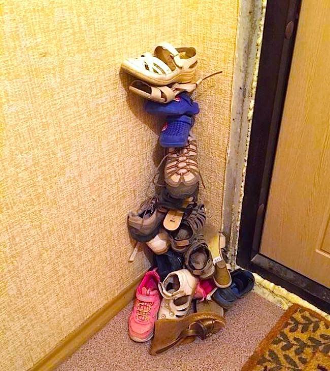 Zapatos ordenados en una torre pegados a la pared