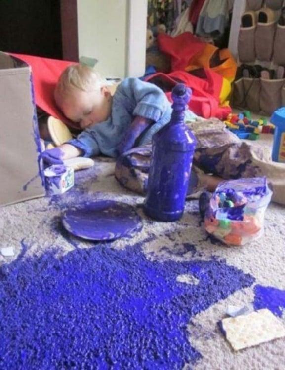 Niño acostado alrededor de muchas cosas en una alfombra llena de pintura