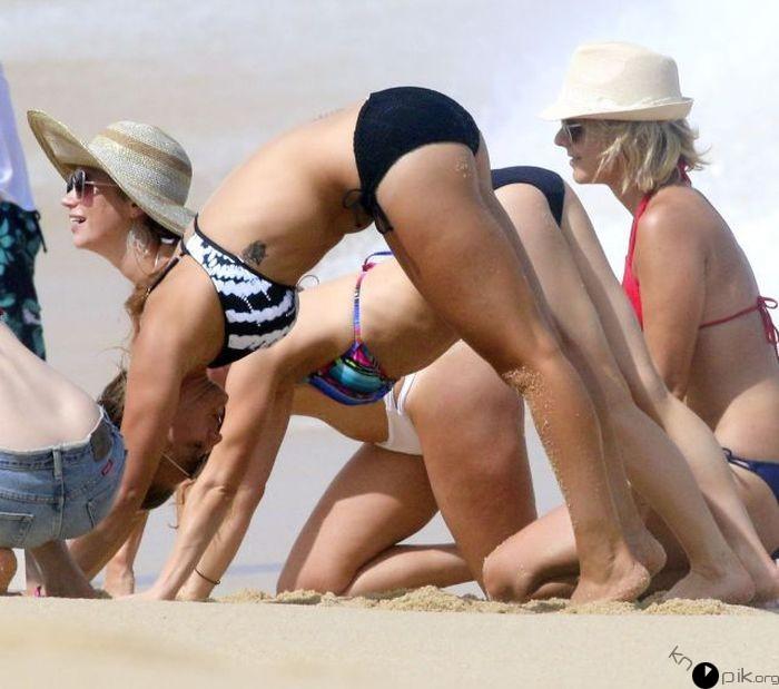 Chicas en una playa con sus piernas y brazos recargadas en la arena