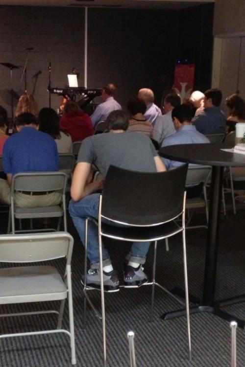 Personas sentadas en sillas frente a un escenario