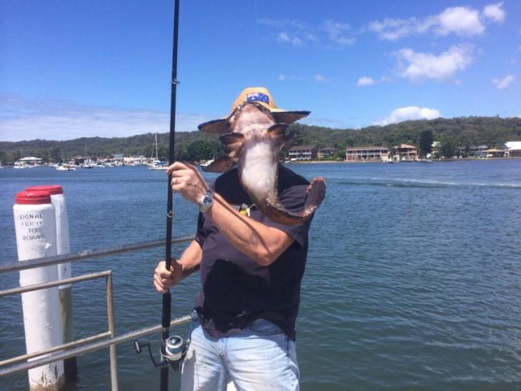 Hombre en el puerto con una caña de pescar y un pez frente a su cara