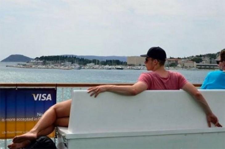 Chico sentado en una banca frente a un puerto que parece tener piernas de mujer