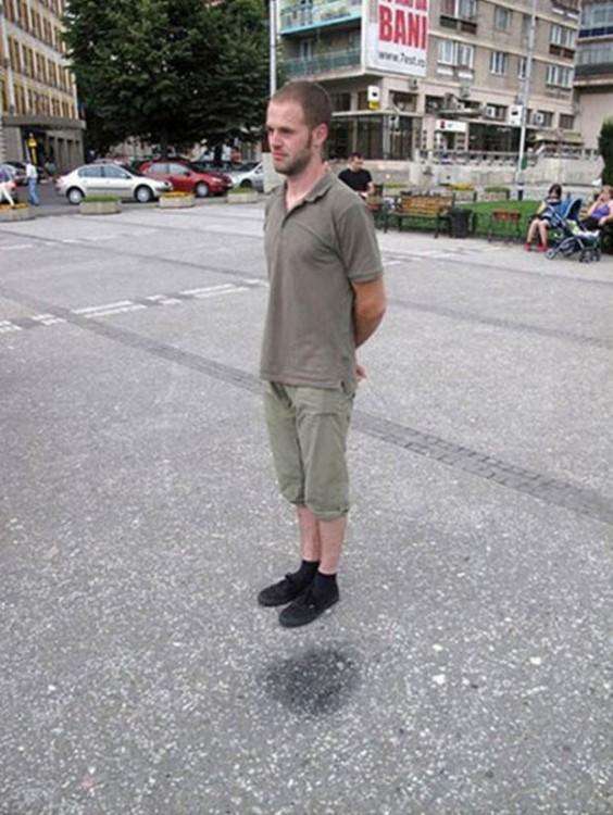 foto de un chico parado en una calle que parece estar flotando sobre el pavimento