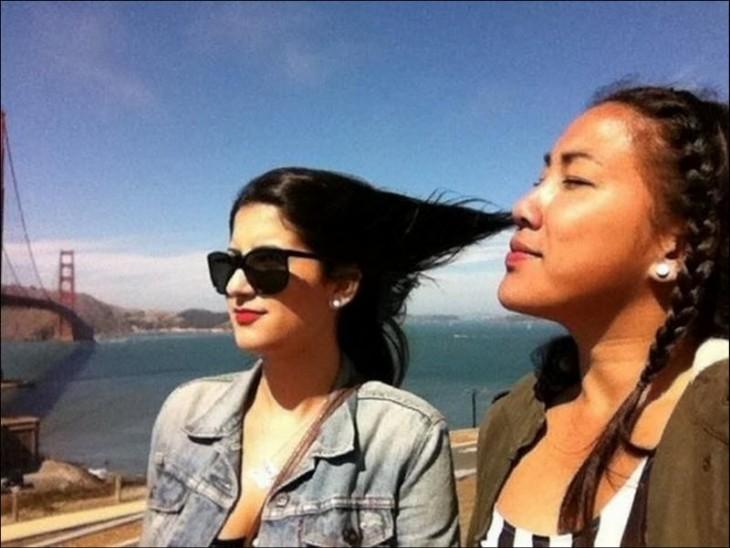 fotografía de una chica que parece estar respirando el cabello de su amiga