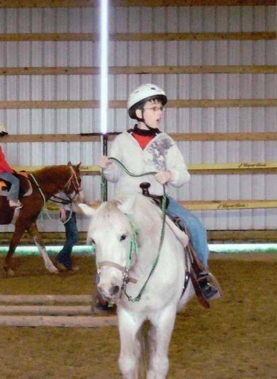 niño montado en un pony en una pose que simula tener un sable de luz en las manos como el de star wars