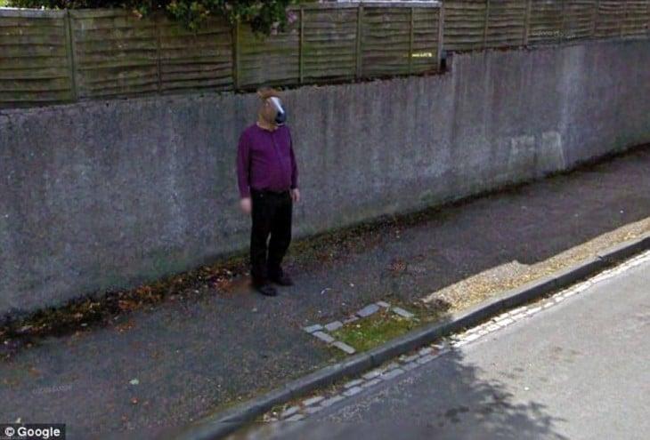 Un hombre en una calle con una cabeza de caballo