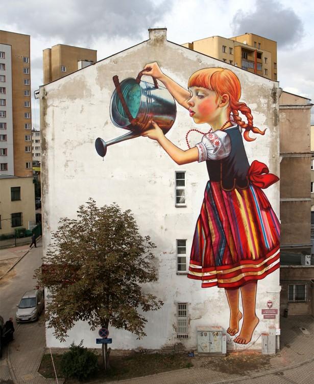Grafiti de una niña en una pared simulando que riega un árbol
