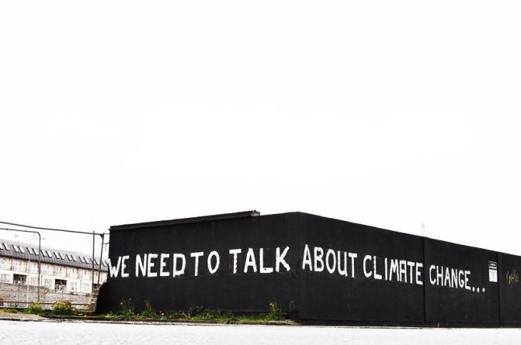 """Frase """"tenemos que hablar del cambio climático"""" pintada en una pared"""