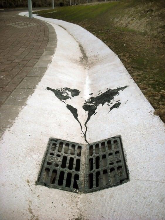 Un mundo dibujado arriba de una coladera en la calle