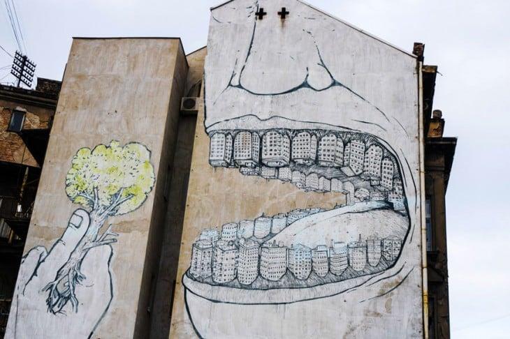 Grafiti de una boca con dientes de edificios consumiéndose un árbol
