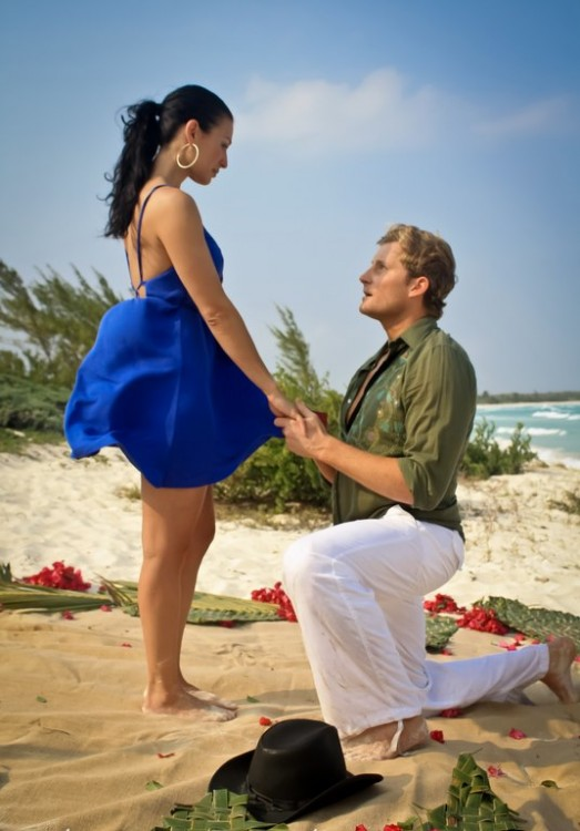 Hombre arrodillado pidiendo matrimonio a una mujer