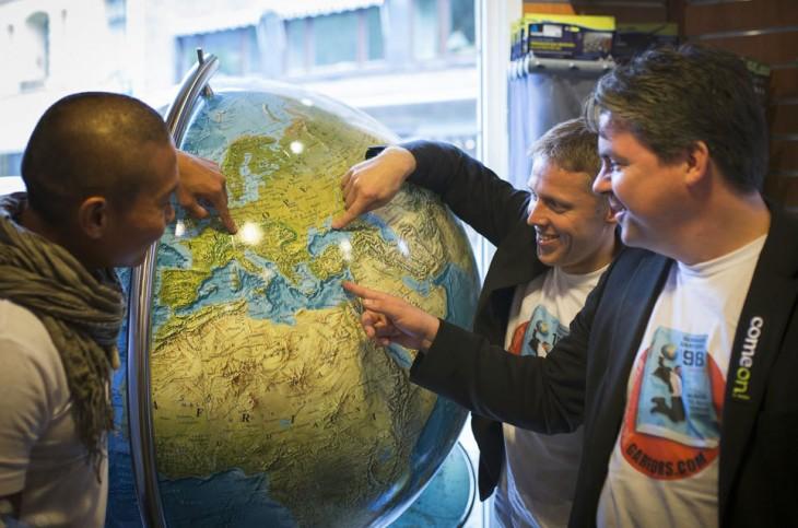 Gunnar y sus amigos señalando en un globo terráqueo