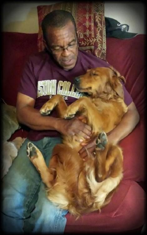 JJ la perra de terapia recargada sobre un hombre en un sillón