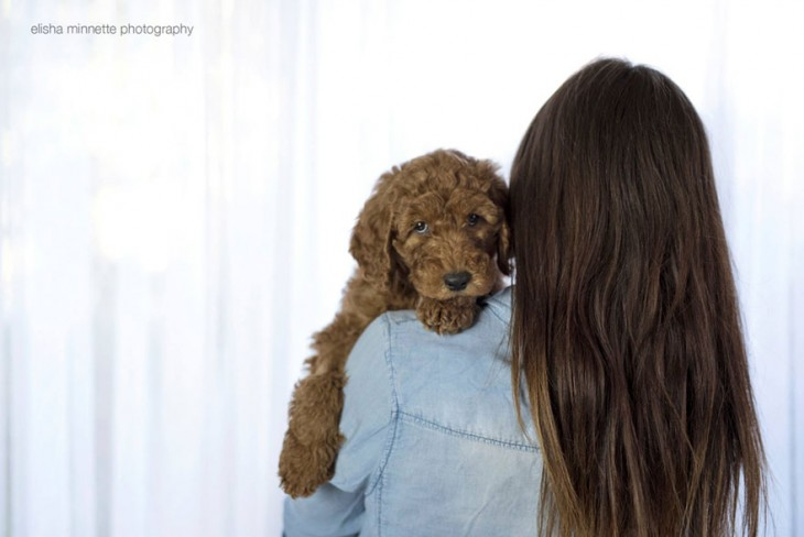 Mujer cargando a un perro con la cabeza recargada en su hombro.
